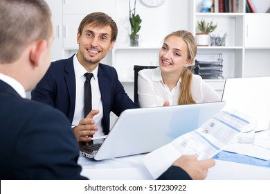 Adult business male and female assistants in formalwear holding paper documents and chatting in company office