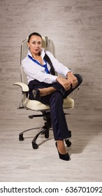 Adult business woman dressed into pants, white blouse, tie posing next to an office chair