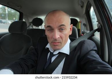 adult businessman behind the wheel of car