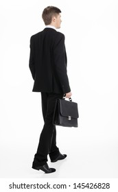 Adult businessman carrying a briefcase walking away
