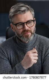 Adult businessman in office. Close-up business portrait of handsome gray hair man wearing eyeglasses sitting at workplace. Confident businessman became successful. Business concept.