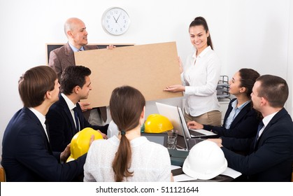 Adult businessman presents new development plan at poster in the office