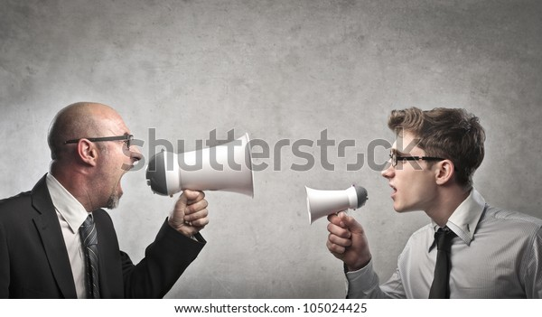 Adult businessman screaming into a megaphone against a younger businessman talking into a smaller one