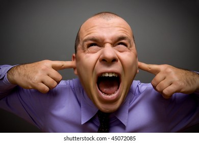 Adult businessman screaming in pain over gray background