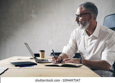 Adult businessman working at modern coworking office.Confident man using contemporary mobile laptop