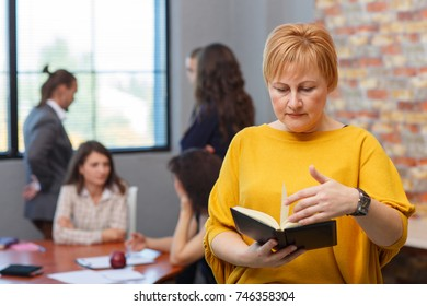 An adult businesswoman looks in a notebook. In the background, office workers.