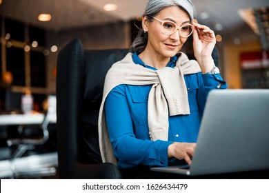 Adult businesswoman sitting in front of a laptop and looking at the screen through the glasses
