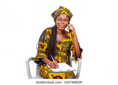 adult businesswoman sitting smiling and talking on the phone while writing in the notebook