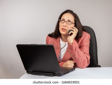 An adult businesswoman wearing a suite on a isolated white background working on a laptop with a phone on her desk looking very frustrated. Social Distancing Concept image