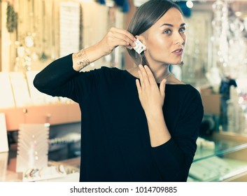 Adult buyer woman choosing a stylish earrings in a jewelry store