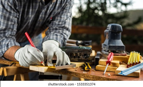 Adult carpenter craftsman wears protective leather gloves, with a pencil and the carpenter's square trace the cutting line on a wooden table. Construction industry, housework do it yourself.