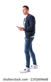 Adult casual man using mobile phone and looking up. Profile view. Full body isolated on white background.
