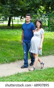 Adult caucasian couple walking in park, sport helps pregnancy