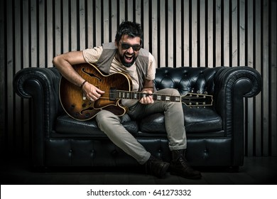 adult caucasian guitarist portrait playing electric guitar sitting on vintage sofa. Music singer concept on couch and modern wood wall