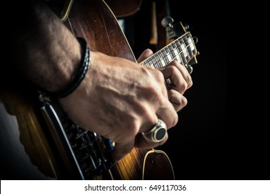 adult caucasian guitarist portrait playing electric guitar on grunge background. Close up instrument detail. Music singer modern concept