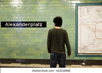 Adult caucasian man waiting on the Alexanderplatz U-Bahn station platform, along with the Berlin city railway map.