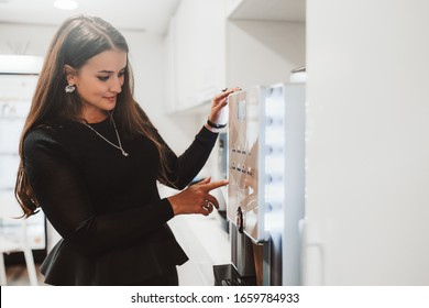 An adult caucasian woman entrepreneur is choosing a type of coffee to prepare while standing indoor of a cozy office coffee point on a kitchen in front of a modern coffee machine