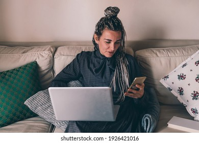 Adult caucasian woman sitting couch indoor at home using comuter and smartphone, chatting and watching video streaming or home banking while remote working