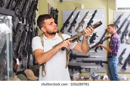 Adult cheerful male is choosing air-powered gun in army market.