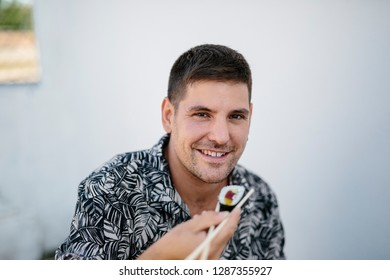 Adult cheerful man taking bite of delicious sushi eating with chopsticks smiling at camera