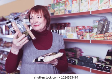 Adult cheerful positive glad smiling woman buyer with assortment of buckwheat food store