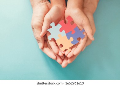 Adult and chiild hands holding jigsaw puzzle shape, Autism spectrum disorder awareness, Autism family support concept, World Autism Awareness Day