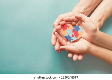 Adult and chiild hands holding jigsaw puzzle heart shape, Autism awareness, Autism spectrum disorder family support concept, World Autism Awareness Day