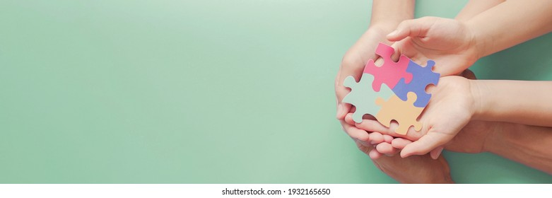 Adult and chiildren hands holding jigsaw puzzle shape, Autism awareness,Autism spectrum disorder family support concept, World Autism Awareness Day