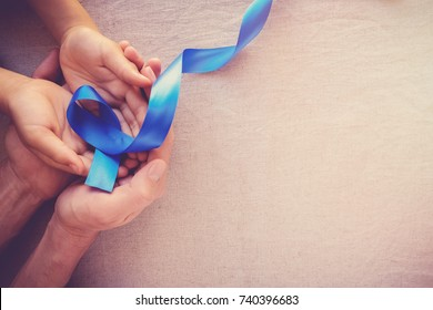 adult and child hands holding Blue ribbon, Colon Cancer, Colorectal Cancer, Child Abuse awareness, world diabetes day, International Men's Day