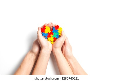Adult and child hands holding colorful heart on white background