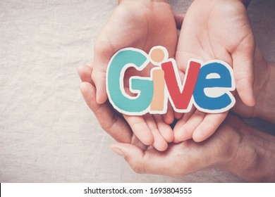 Adult and child hands holding Give word, kind, donate, charity and compassion concept