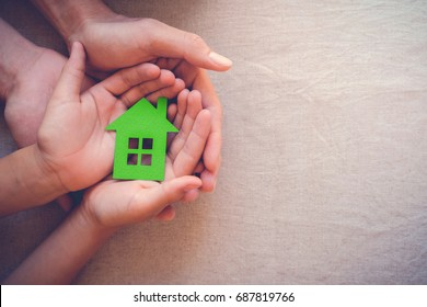 Adult and child hands holding green paper house, eco house, family home, house insurance concept, zero waste, green sustainable living