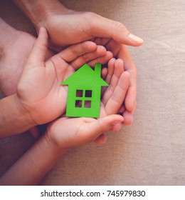 Adult and child hands holding green paper house, eco house concept