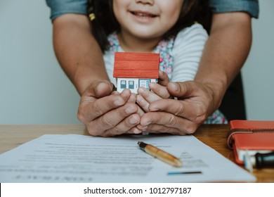 Adult and child hands holding house model  family home, homeless housing and real estate, insurance concept