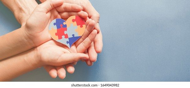 Mains adultes et enfants tenant une forme de coeur de puzzle, sensibilisation à l'autisme, concept de soutien familial du spectre autistique, Journée mondiale de sensibilisation à l'autisme
