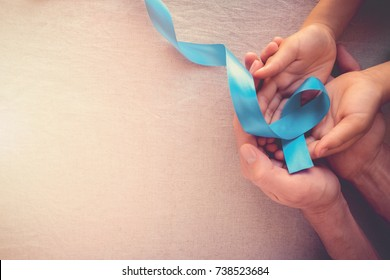 Adult and child hands holding Light blue, sky blue ribbons, toning background, Prostate Cancer Awareness and Adrenocortical carcinoma awareness, Men's health care concept