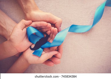 Adult and child hands holding Light blue ribbons with mustache , Prostate Cancer Awareness, Men health awareness