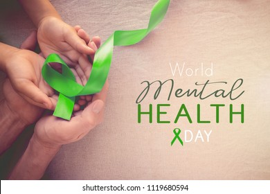 Adult and child hands holding Lime GreenRibbon, world Mental health day