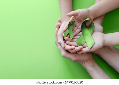 Adult and child hands holding Lime Green Ribbon on green background, children Mental health awareness and Lymphoma Awareness, world mental health day, world kidney day, organ donation