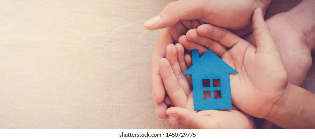 Adult and child hands holding paper house, family home, homeless shelter and real estate concept, international day of families