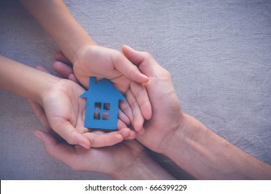Adult and child hands holding paper house, family home, homeless housing shelter and real estate, insurance concept