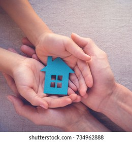 Adult and child hands holding paper house, family home, homeless shelter and real estate concept