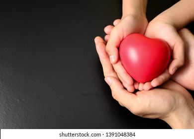 adult and child hands holding red heart, health care, donate and family insurance concept,world heart day, world health day
