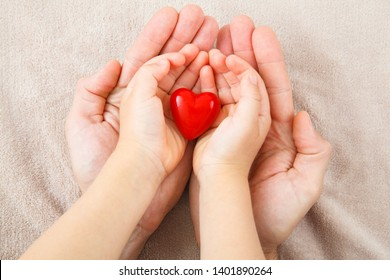 adult and child hands holding red heart, health care, donate and family insurance concept,world heart day, world health day, CSR concept