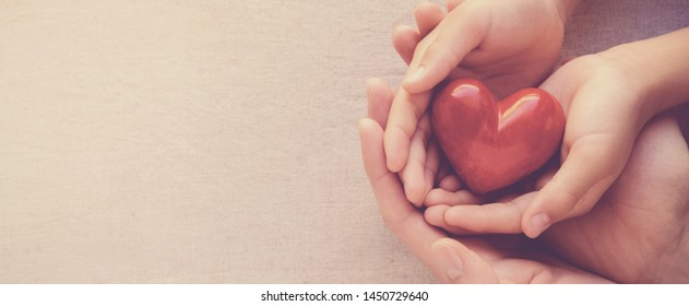 adult and child hands holding red heart, heart health and happy charity donation concept, world mental health day, world heart day, fair trade