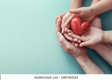 adult and child hands holding red heart, heart health, donation, happy volunteer charity, CSR social responsibility concept, world heart day, world health day, world mental health day, family day