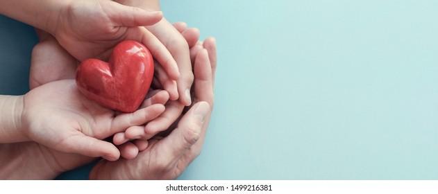 erwachsene und kinderreiche Hände, die rotes Herz auf Aquakulturhintergrund halten, Herzgesundheit, Spende, CSR-Konzept, Weltherztag, Weltgesundheitstag, Familientag, fairer Handel, Pflegekonzept