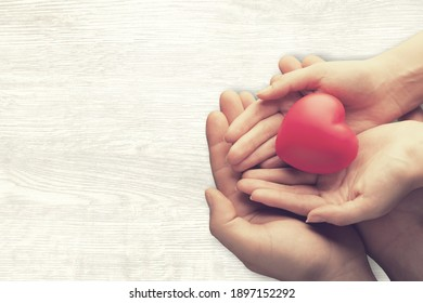 Adult and child hands holding the red heart
