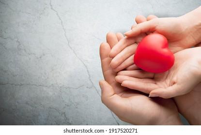 Erwachsene und Kinder, die rotes Herz auf Hintergrund halten