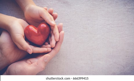 adult and child hands holding red heart, health care, love and family insurance concept, world heart day, world health day